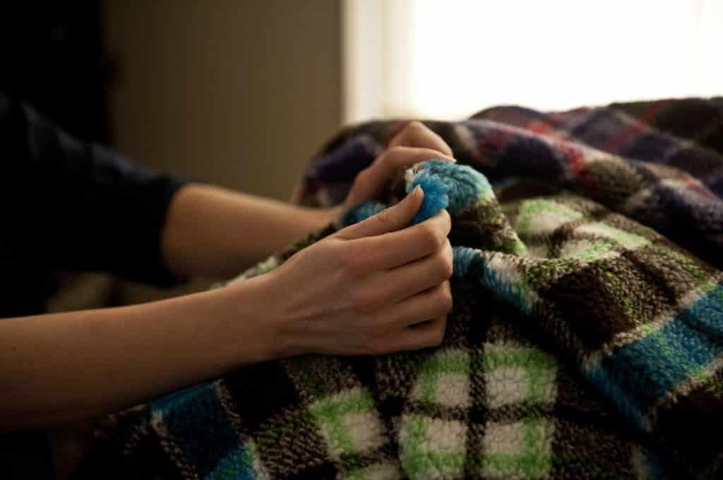 mani che toccano tessuto agnellino
